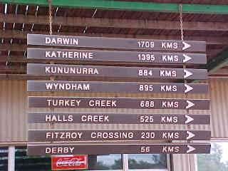 Sign reads: Darwin 1709k, Katherine 1395k, Kununurra 884k, Wyndham 895k, Turkey Creek 688k, Halls Creek 525k, Fitzroy Crossing 230k, Derby 56k