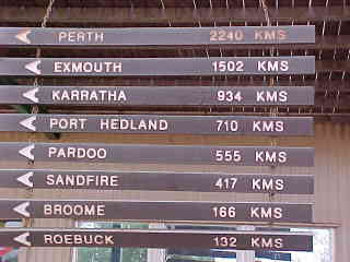 Sign reads: Perth 2240k, Exmouth 1502k, Karratha 934k, Port Hedland 710k, Pardoo 555k, Sandfire 417k, Broome 166k, Roebuck 132k