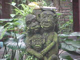 Statue of 3 monkeys; Mommy, Daddy and child.  There is a Hindu offering of food in a plate on their heads