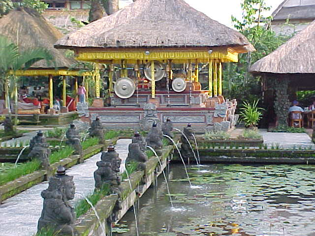 looking over the pond past the fountains to the gongs at the Palace restaurant in Ubud, Bali