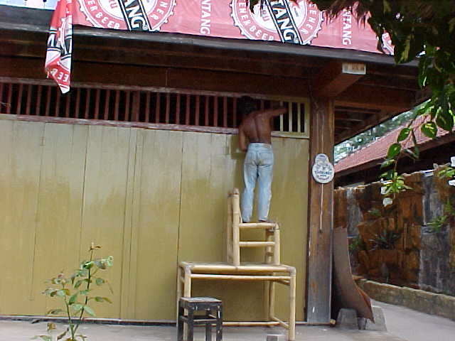 One of the workers at Melati painting the vents on the resturant