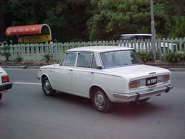 "Look familure Dad? But shouldn't the number plate read ""366 BAU""? : My father used to have one of these.  It's a 1970 ""Toyota Corrolla Deluxe"".  It is the first car I ever drove on a regular basis.  It has a snappy 1900cc engine and 4 on the floor. (Malaysia, The Travel Addicts)"