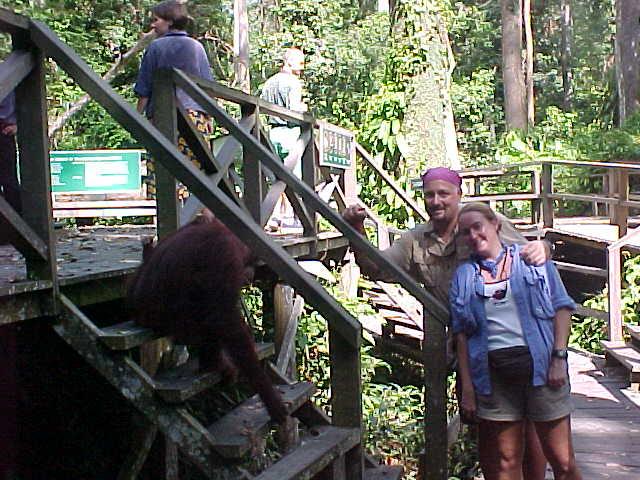 "MVC-009S-Us and orangutan. Michael Alessio ""MRA"", and SaraGrace Keenan. Sepilok Orangutan Rehabilitation Centre, Sabah, Malaysia (The Travel Addicts, Malaysia)"