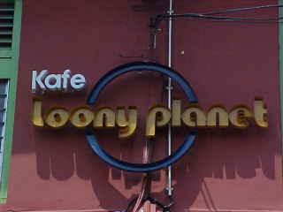 Mvc-158e-Resturant Kafe loony planet. Malacca, Malacca, Negeri Melaka, Malaysia: The Lonely Planet series of guidbooks is the de-facto standard amongst backpakers worldwide.  Many enterprising locals take advantage of this fact as this creative pun of a resturant name shows. (Malaysia, The Travel Addicts)
