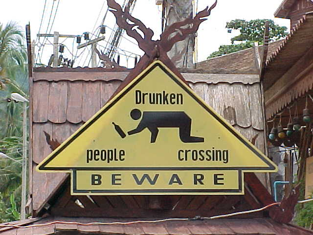 Sign in Lamai : Sign says: Drunken people crossing.  \ Beware (Thailand, The Travel Addicts)