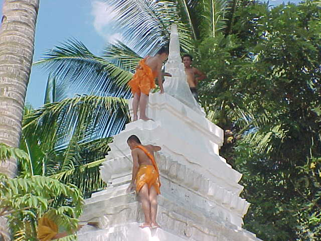 Monks whitwashing a stupa (Laos, The Travel Addicts)