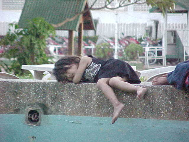 Laotian girl sleeping on fountain in centre of city (Laos, The Travel Addicts)