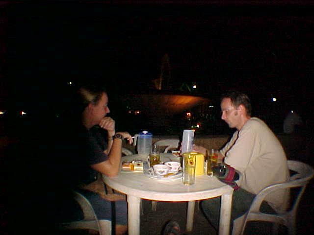 SGK and our friend Mike at dinner in front of that fountain (Laos, The Travel Addicts)