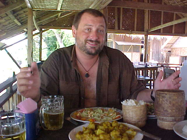 Michael enjoying Laap, Papaya salad, sticky rice, and pumpkin curry (Laos, The Travel Addicts)