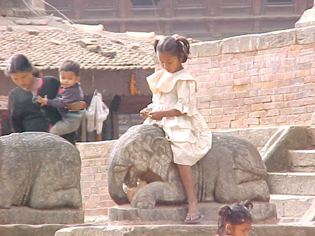 Little girl enjoying elephant statue (Nepal, The Travel Addicts)