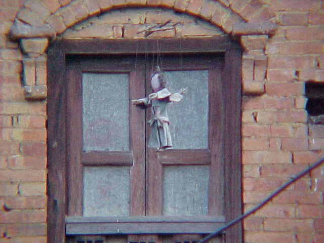 Dolls hanging from eaves (Nepal, The Travel Addicts)